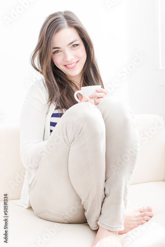 Attractive young woman drinking coffee in couch