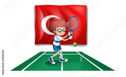 A boy playing tennis in front of the flag of Turkey