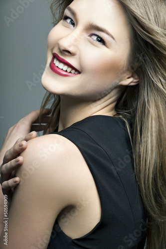 beautiful smiling girl with perfect skin on a dark background