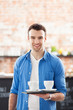 Waiter holding cups of coffee in cafe