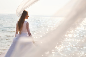 Bride near waterline with Long flying veil