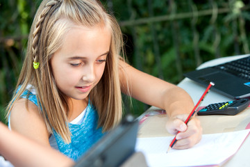 Cute girl doing schoolwork outdoors.