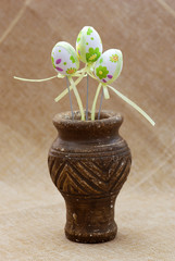 Ornamental easter eggs in a clay vase