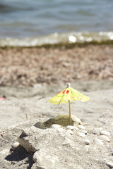 Small paper umbrella on beach near sea shells