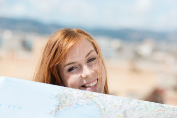 lachende frau schaut über landkarte