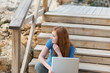 frau sitzt draußen mit laptop