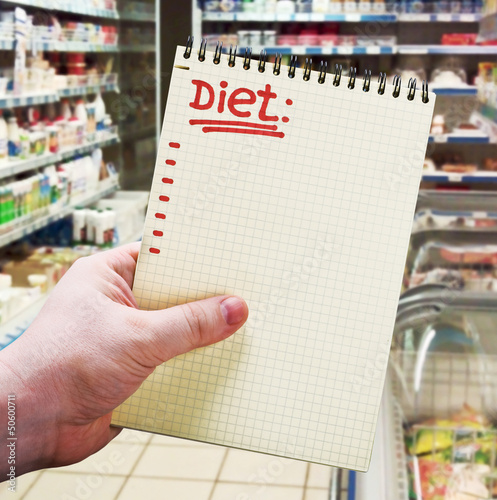 hand holds a notebook with diet plan