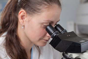 Young female doctor with microscope
