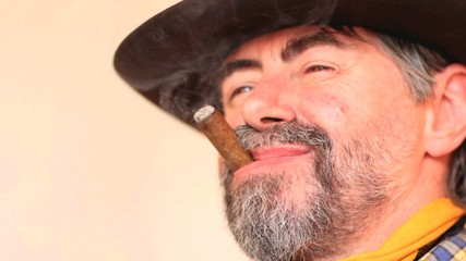 Closeup portrait of cowboy smoking cigar and laughing.