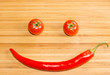 Happy face made of two tomatoes and a chili pepper