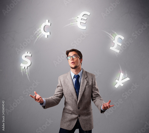 young man standing and juggling with currency icons