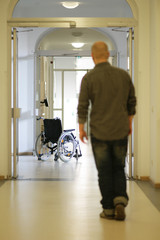 Mann hinter Rollstuhl