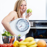 Girl with scale and fruits in kitchen is proud to lose weight