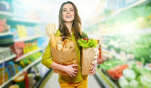 Young woman holding a grocery bag full of bread - 50606315