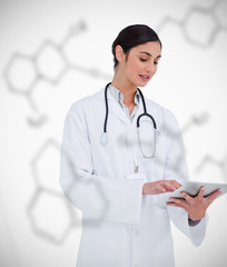 Doctor using tablet pc on chemical formula background