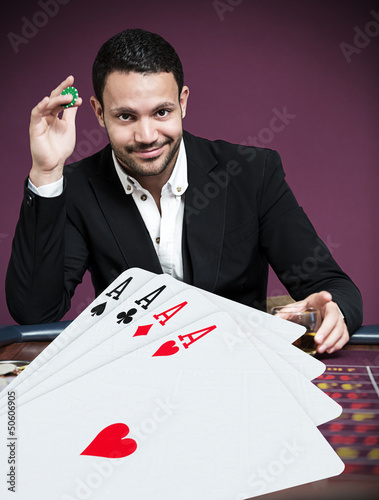 Handsome gambler betting on four aces