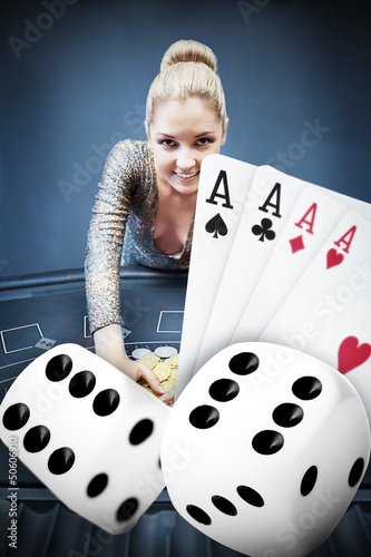 Blonde woman grabbing chips with digital hand of four aces and d