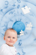 Portrait of a baby with globe and jigsaw pieces background