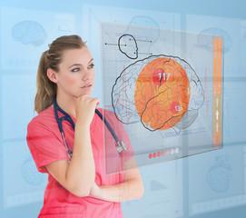 Thoughtful nurse using a futuristic interface