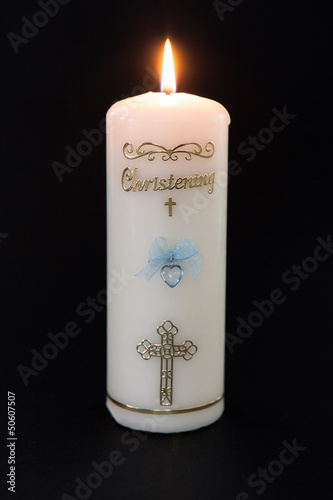 Lit white christening candle with blue detail