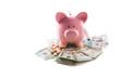 Piggy bank tablets and syringe resting on pile of dollars