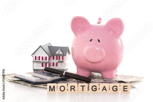 Piggy bank beside calculator miniature house and mortgage spelle