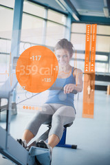 Front view of a girl on rowing machine with futuristic interface