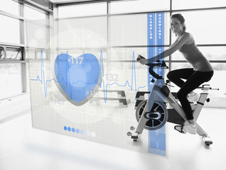 Young attractive girl doing exercise bike with futuristic interf