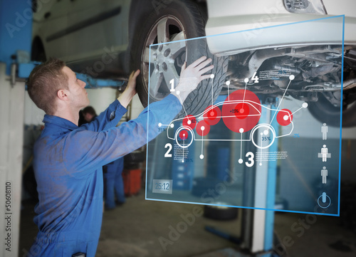 Mechanic checking wheel of a car helped by interface