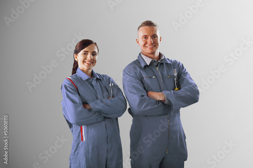 Two mechanics standing on grey background