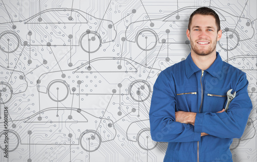 Young mechanic standing in front of cars background