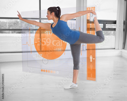 Brunette in yoga pose with futuristic interface next to her