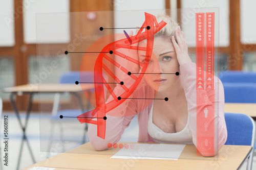 Blonde woman thinking hard while studying on futuristic interfac