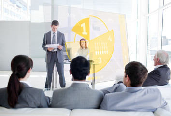 Business people listening and looking at yellow pie chart interf