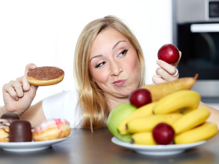 Pretty woman dithers between fruits or sweets