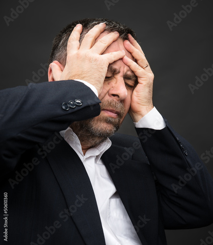 Headache. Man with face closed by hands