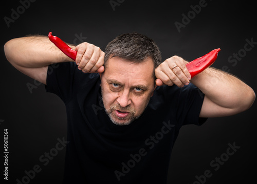 elderly man holding two red hot chili peppers
