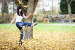 Young girl kicking some autumn leaves. Outdoor.