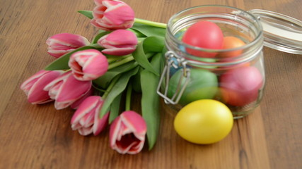 Rack focus on glass tulip bunch and Easter eggs