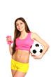 Cute fitness girl posing with dumbbells and a soccer ball on a w