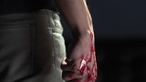 Pan down of man holding bloody knife
