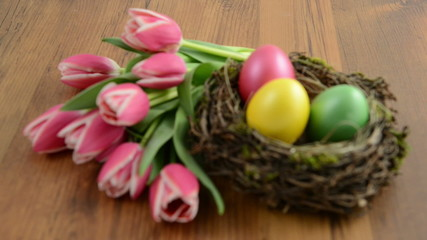 Easter eggs in bird nest with bunch of pink tulips
