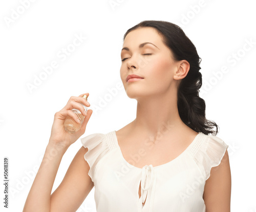 woman spraying perfume on her neck