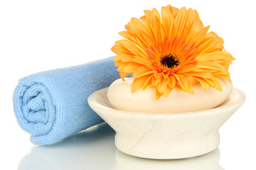 Rolled blue towel, soap bar and beautiful flower isolated