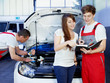 Car mechanics and customer look at the service record