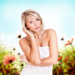 attraktive junge blonde Frau vor Blumenfeld