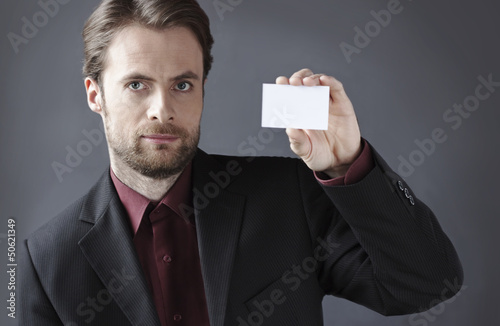 Serious businessman presenting blank business card