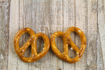 Two pretzel hearts on wooden background
