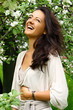 Beautiful woman laughing by blossoming tree