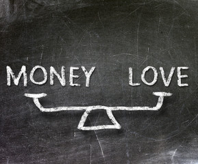 Balance of money and love on blackboard